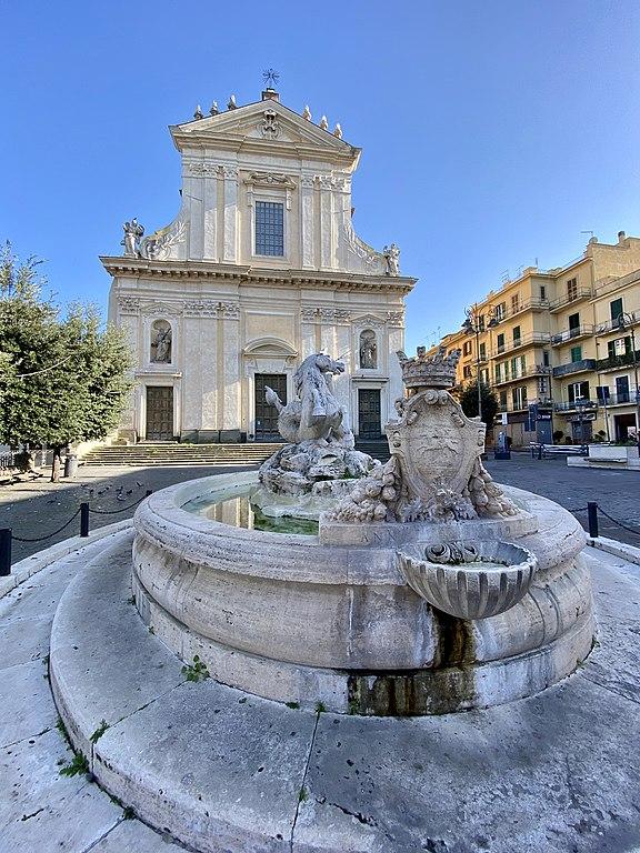 Foto della Fontana del Tritone. Sullo sfondo la Basilica di San Barnaba nella piazza omonima del centro storico di Marino, comune sui Colli Albani nell'area dei Castelli Romani.