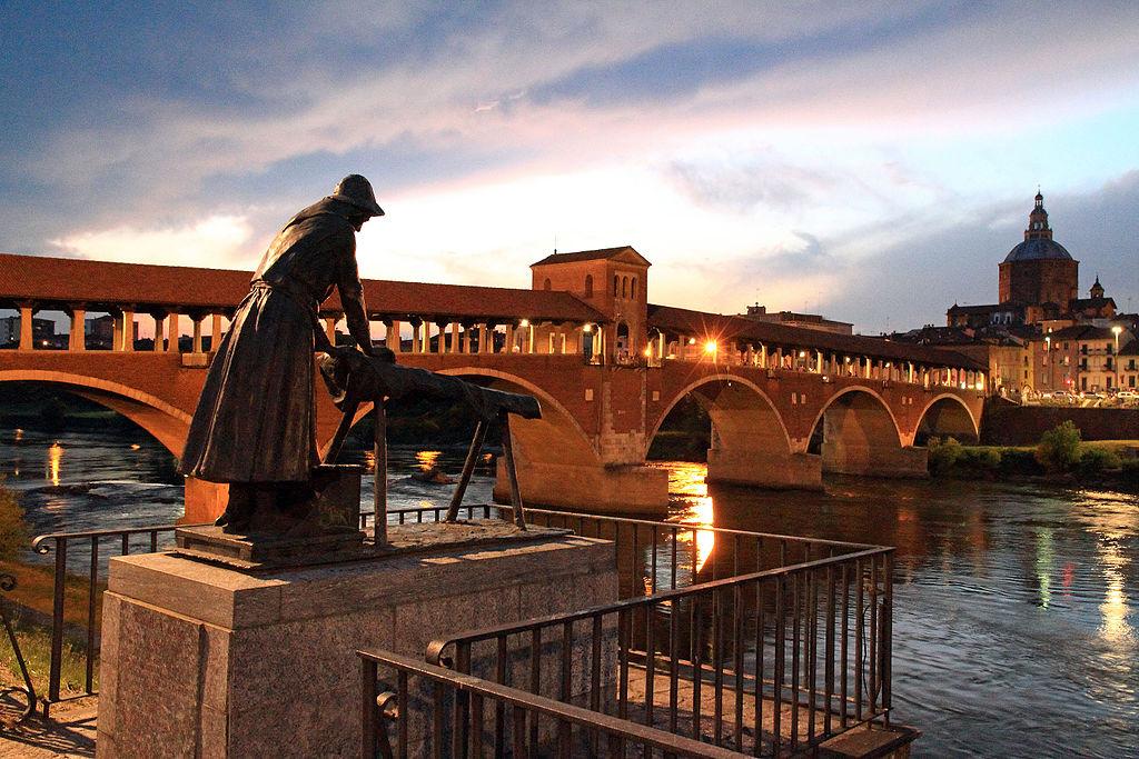 Suggestiva immagine di Pavia con la Statua della Lavandaia in primo piano, il Ponte Coperto sul fiume Ticino e, sullo sfondo, la cupola del Duomo